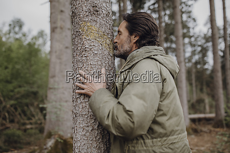 mature hiker kissing tree trunk