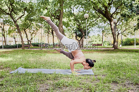 mid adult woman practising yoga on