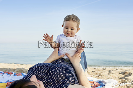 cute smiling boy sitting on mothers