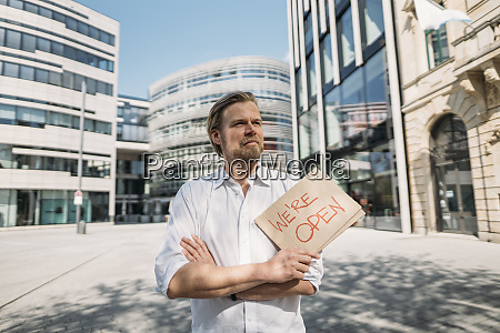 shopkeeper holding cardboard with opening announcement