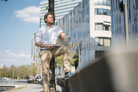 businessman using laptop in the city