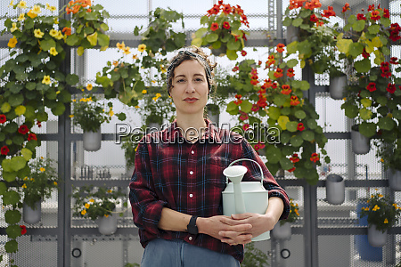 portrait of woman holding watering can