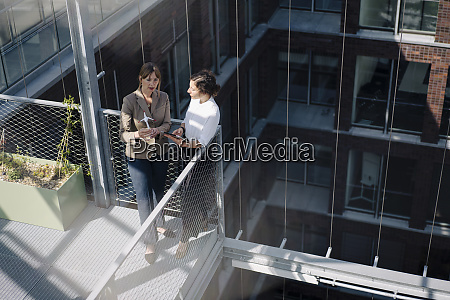 two businesswomen with tablet and wind