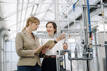 two businesswomen with clipboard and model