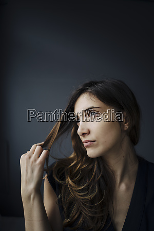 portrait of daydreaming young woman against