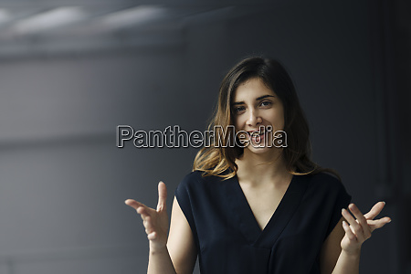 portrait of gesturing young businesswoman against