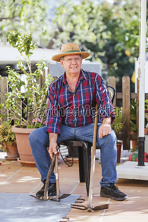 senior man with gardening tools sitting