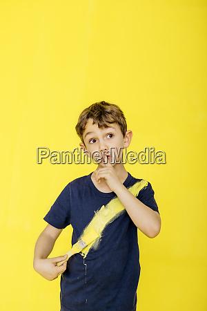 cute boy using paintbrush on t