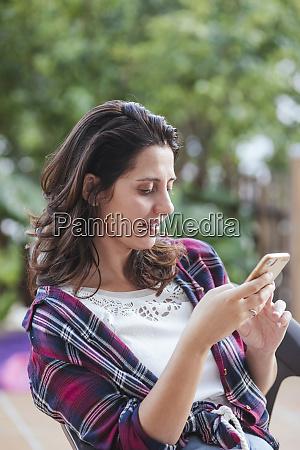 woman using smartphone in garden
