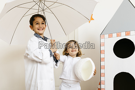 siblings playing astronaut and researcher with
