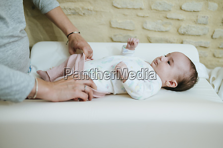 mother undressing her baby on changing