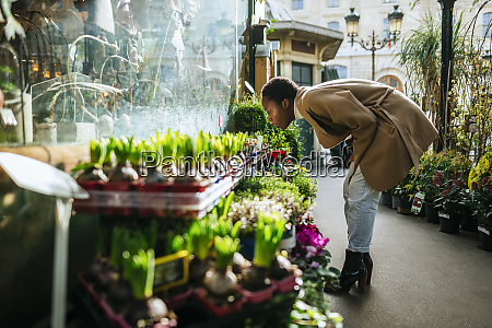 woman smelling flowers at market in