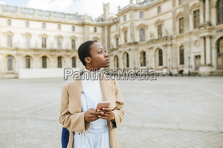 thoughtful woman holding smart phone at
