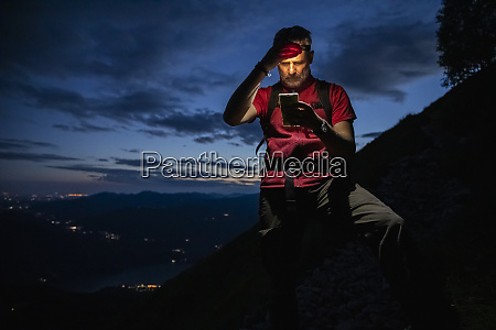 male hiker checking map over smart