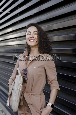 contented businesswoman carrying laptop bag while