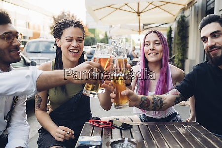 happy friends clinking beer glasses outdoors