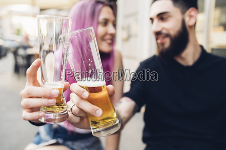 happy young couple clinking beer glasses