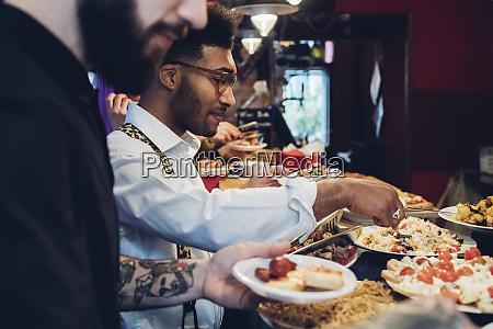 friends taking food from buffet in