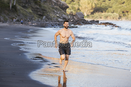 handsome shirtless mid adult man running