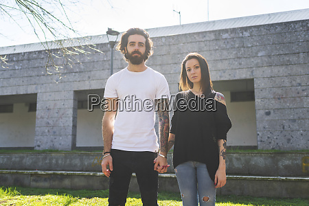 couple holding hands while standing against