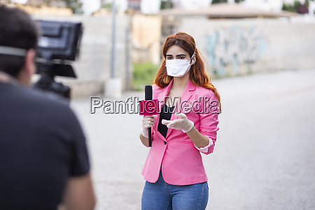 man filming reporter wearing mask while