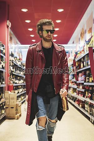 bearded man wearing sunglasses walking in