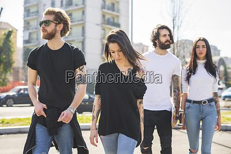 stylish friends walking in city on