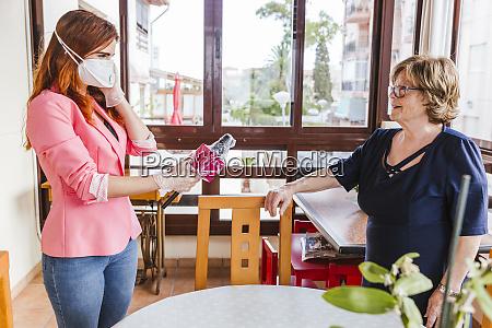 female reporter wearing mask interviewing senior