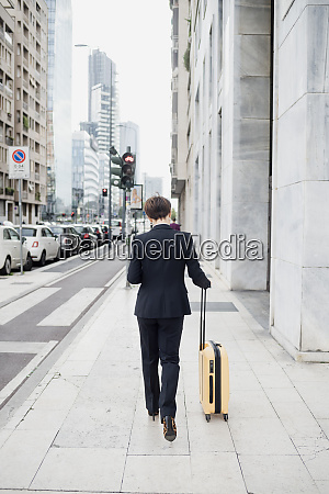 female professional with suitcase walking on