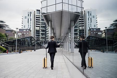 female entrepreneur holding suitcase using smart