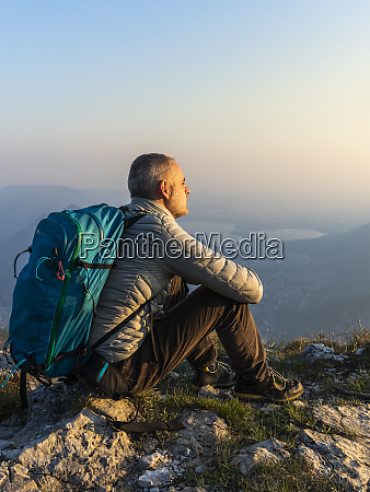 hiker sitting on viewpoint orobie alps