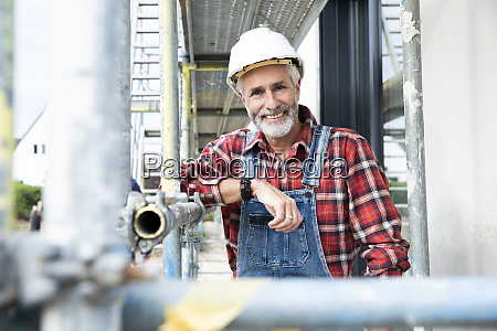 smiling male architect wearing overalls standing