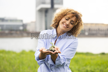 smiling businesswoman with curly hair holding