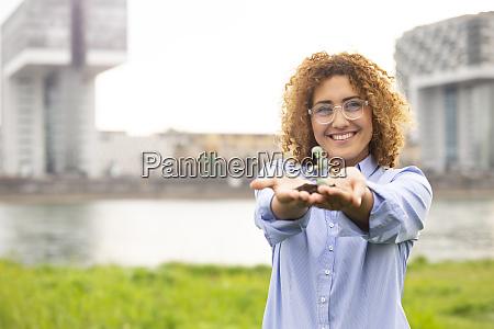 businesswoman wearing eyeglasses holding small plant