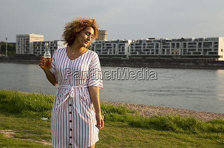mid adult woman holding beer bottle