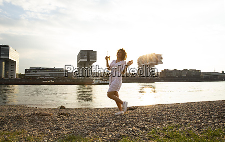 carefree woman holding beer bottle dancing