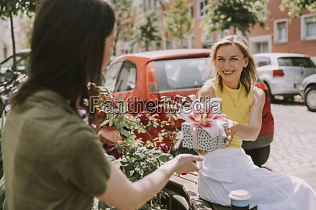 smiling woman handing over gift to