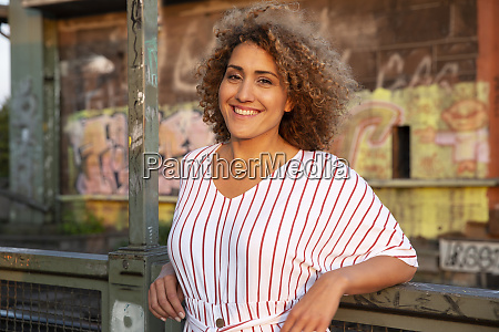 cheerful woman with curly hair standing