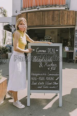 cafe owner wearing face mask posting