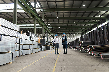 two businessmen talking in a factory