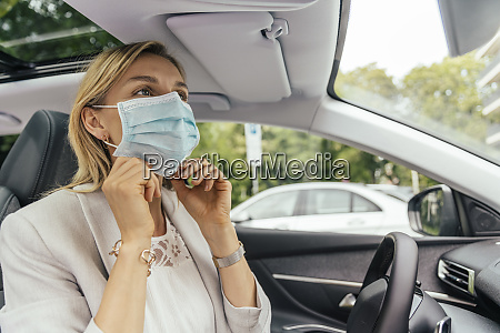 portrait of woman in car putting