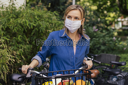 woman wearing face mask with bicycle