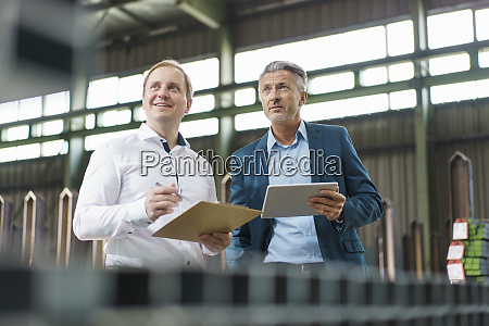 two businessmen with tablet and clipboard