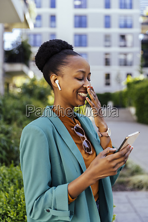 laughing businesswoman using her smartphone and