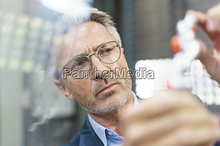 portrait of mature businessman examining industrial