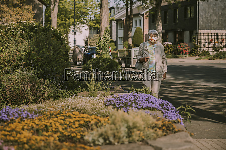 senior woman walking by plants on