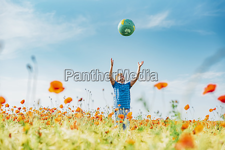 boy catching globe while standing in