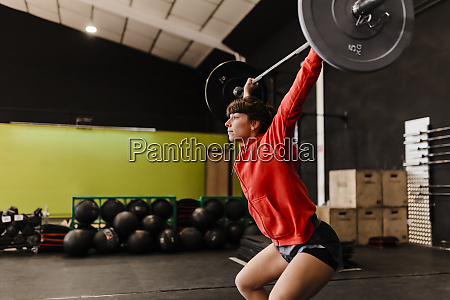female athlete lifting deadlift while standing