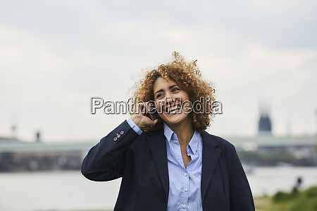 businesswoman using smartphone at riverside in