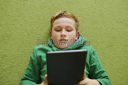 boy using digital tablet on green